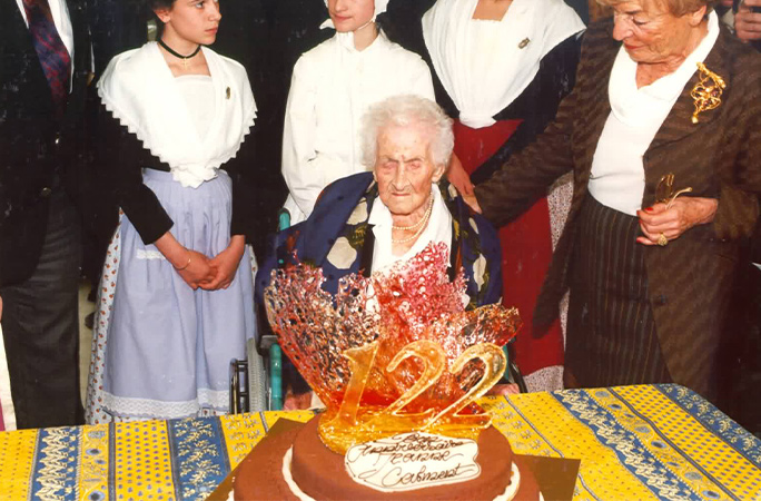 Jeanne Calment celebrating her 122nd birthday with cake on table